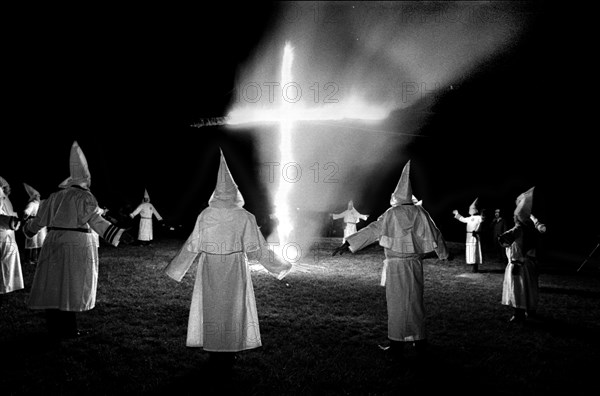 Members of the KKK circle a cross lighting in Rumford Me during rally in the small town Maine town. The Klan had been active in Maine in the 1920's and 30's , This group of Klansmen openly invited the press to observe ,photograph and report on this event photo by bill belknap