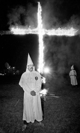 A Member of the KKK stands next to cross lighting in Rumford Me during rally in the small town Maine town. The Klan had been active in Maine in the 1920's and 30's , This group of Klansmen openly invited the press to observe ,photograph and report on this event photo by bill belknap