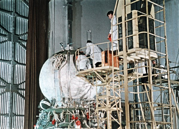 Work being done on the vostok 1 capsule in preparation for gagarin's historic flight, 1961, this is a still from a soviet film about the space program.